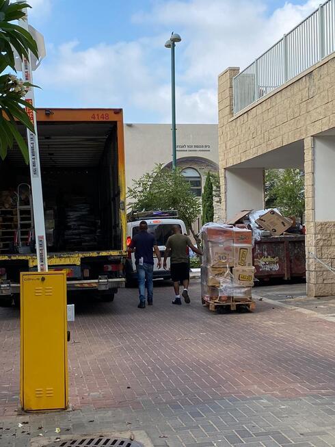 משאיות פורקות סחורה במיני מרקט