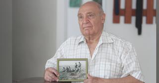 עזרא משקיף-עינצ'י מחזיק את תמונת אחיו וחבריו לנשק   צילום: אסף פרידמן